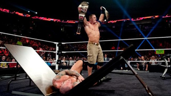 John n CEna Showing Two Tittles After Smashes Orton On Table